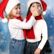 Little girl in a Santa Claus cap, closes his mouth palm boy — Foto Stock
