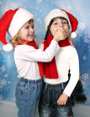 Little girl in a Santa Claus cap, closes his mouth palm boy — Stock Photo