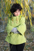 Beautiful girl in the green coat in the branches of willow autum — Stock Photo