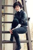 Neveselé dívka v černém na kovovém žebříku — Stock fotografie