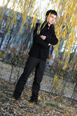A guy in a black coat on green willow autumn — Stock Photo