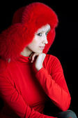 Beautiful girl in a red fur hat on a black background — Stock Photo