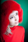 Hermosa chica en un sombrero de piel roja con un fondo verde — Foto de Stock