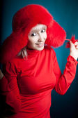 Beautiful girl in a red fur hat on a blue background — Stock Photo