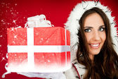 Santas helper holding sparkly Christmas present — Stock Photo