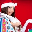 Portrait of a santa woman with shopping bags — Stock Photo