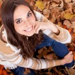 Closeup of a woman in autumn leaves — Stock Photo