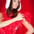 Furry hat and red feather on xmas girl - Stock Photo