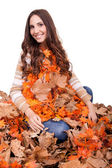 Happy woman covered with autumn leaves — Stock Photo
