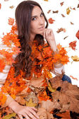 Attractive woman in a pile of autumn leaves — Stock Photo