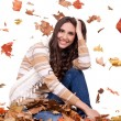 Autumn woman in a colorful pile of leaves — Stock fotografie