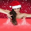Sexy  santa woman sprinkling snow on board — Stock Photo