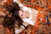 Beautiful woman lying on autumn leaves — Stock Photo
