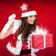 Santa girl adding little magic to Christmas present — Stock Photo