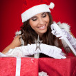Santa girl wrapping chrsitmas present — Stock Photo