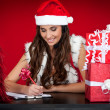 Santa girl making list of christmas present wishes — Stock Photo