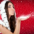 Attractive girl in Christmas costume blowing snow form hand — Stock Photo