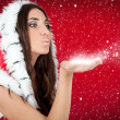 Attractive girl in Christmas costume blowing snow form hand — Stock Photo #4458766