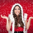 Santa girl enjoying the way it snows — Stock Photo #4458835