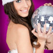 Woman in santa costume holding disco ball - Stockfoto