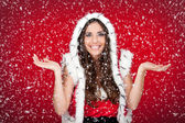 Santa girl enjoying the way it snows — Stock Photo