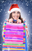 Winter woman with santa hat holding shopping bags — Stock Photo