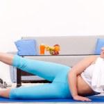 Teenage girl exercising home — Stock Photo