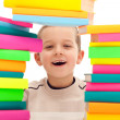 Boy behind pile of books — Stockfoto