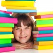 Girl sitting behind pile of books — Stock fotografie