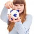 Teenage girl putting coin in piggy bank — Stock Photo