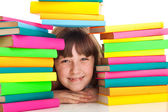 Girl sitting behind pile of books — Stock Photo