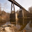 Old railroad bridge over a creek vertical - Stockfoto