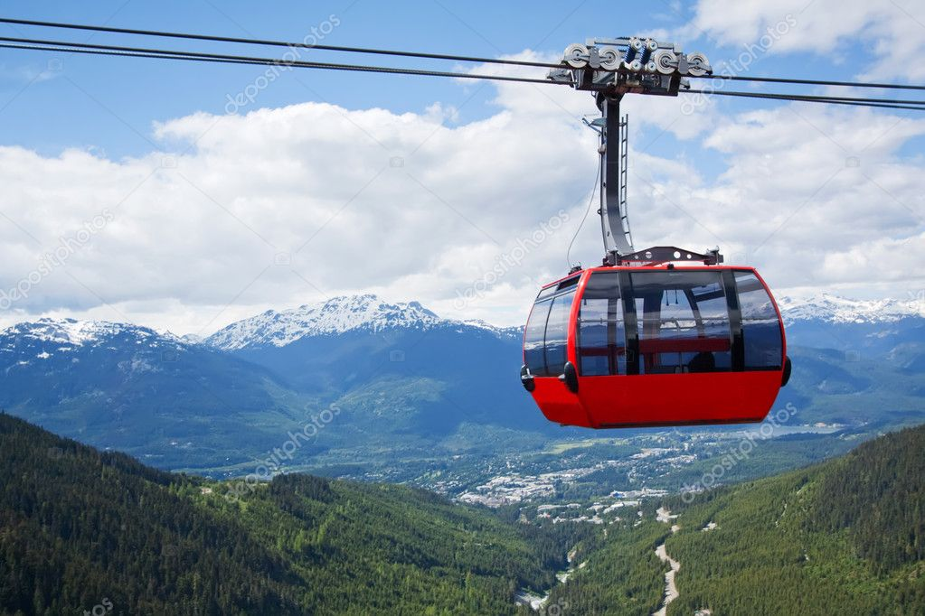 Red car of the aerial tramway connecting two high peaks at Whistler Mountain in British Columbia, Canada with blue sky and white clouds — Stock Photo #4203655