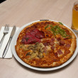 Four seasons type of pizza with a place setting for one and beer — Stock Photo