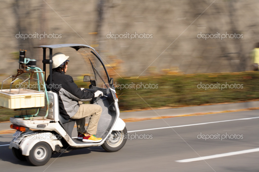 Panning image of a food delivery man with scooter in motion. — Stock Photo #4821325