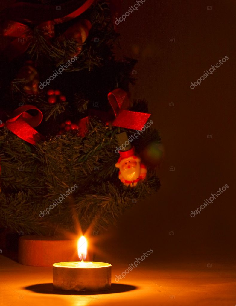 A burning candle and in background a litte Christmas tree in a warm atmosphere  Stock Photo #4900167