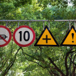 Four road signs with warning and speed limit - Stock Photo
