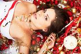 Krásná brunetka ležící mezi vánoční dekorace — Stock fotografie