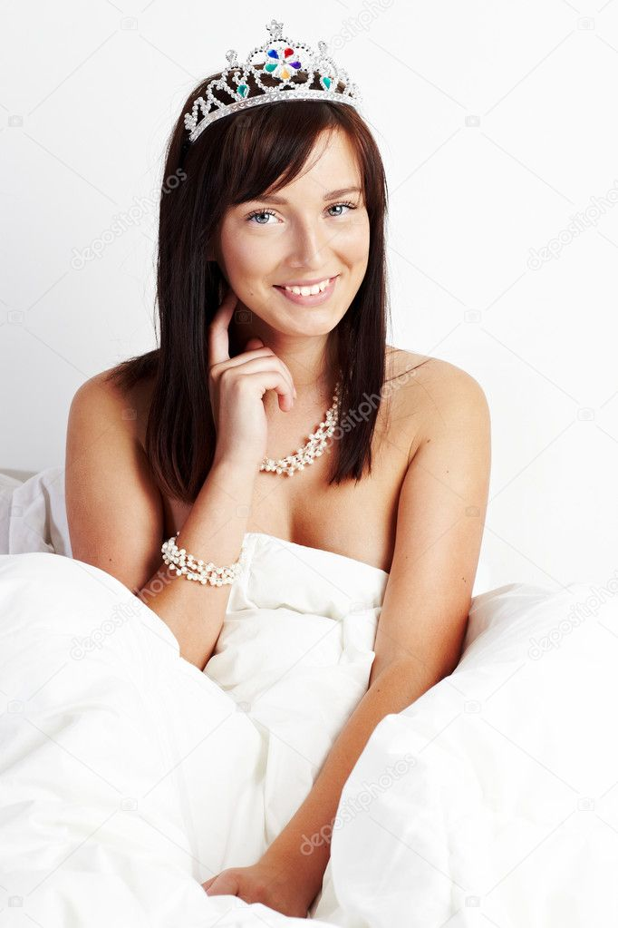 Young beautiful woman wearing toy crown sitting on white bed  — Stock Photo #4158005
