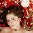 Beautiful brunette lying among Christmas decoration — Stock Photo