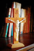 Wooden crucifix on book shelf — Stock Photo