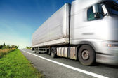Silver truck driving on country road — Stockfoto