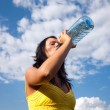 Girl drinking water from a bottle — Stock Photo