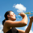 Young girl drinking water from a bottle — Stock Photo