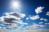 Sun in a blue cloudy sky — Stock Photo
