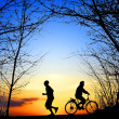 Recreation, jogging and cycling at sunset — Stock Photo
