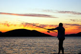 Silhouette of fisherman at sunset — Stock Photo