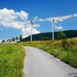 Country mountain road and wind turbines - Stock Photo