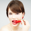Sexy woman biting a chili pepper — Stock Photo