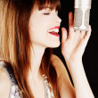 Girl singing to the microphone in a studio — Stock Photo #5152110